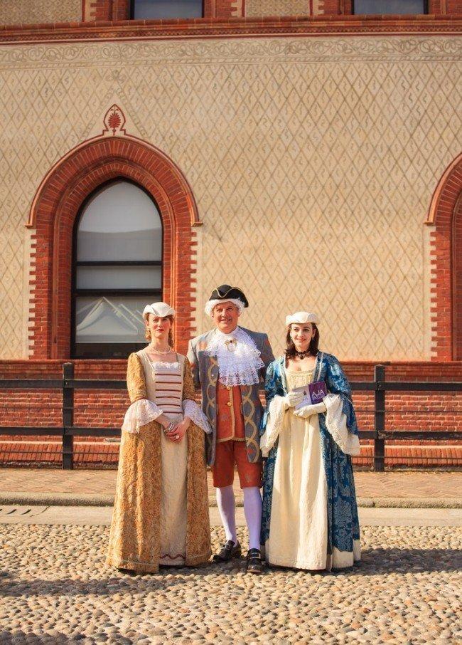 Люди в костюмах XVII века на фоне фасада здания
