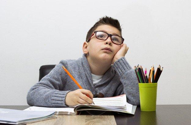 Мальчик делает домашку за деньгим другим школьникам