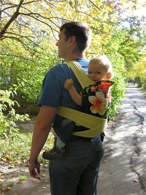 ребенок в слинге на прогулке с папой
