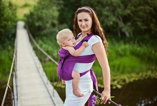 ребенок в слинге с мамой на прогулке