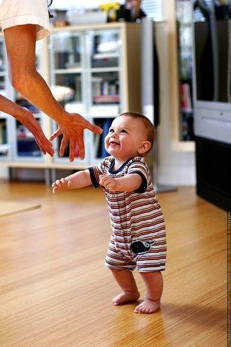 Ребенок идет без поддержки на ручки к маме